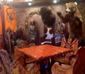 A small area near the bar features carved wood tables and chairs, wooden Indians and a grizzly bear.